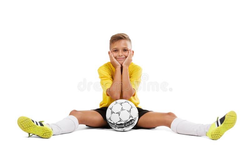 Ένας χαριτωμένος νέος αθλητικός τύπος σε μια κίτρινη μπλούζα και μαύρα σορτς που κάθονται σε ένα πάτωμα που απομονώνεται σε ένα ά στοκ φωτογραφία με δικαίωμα ελεύθερης χρήσης