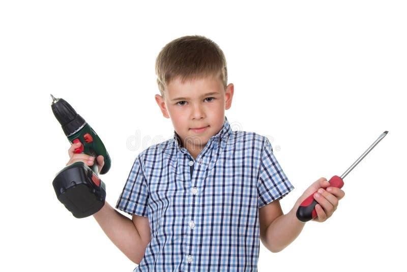 Ένας χαριτωμένος οικοδόμος αγοριών στο ελεγμένο πουκάμισο καταδεικνύει τη δυσκολία ένα εργαλείο, που απομονώνεται στο άσπρο υπόβα στοκ φωτογραφία με δικαίωμα ελεύθερης χρήσης
