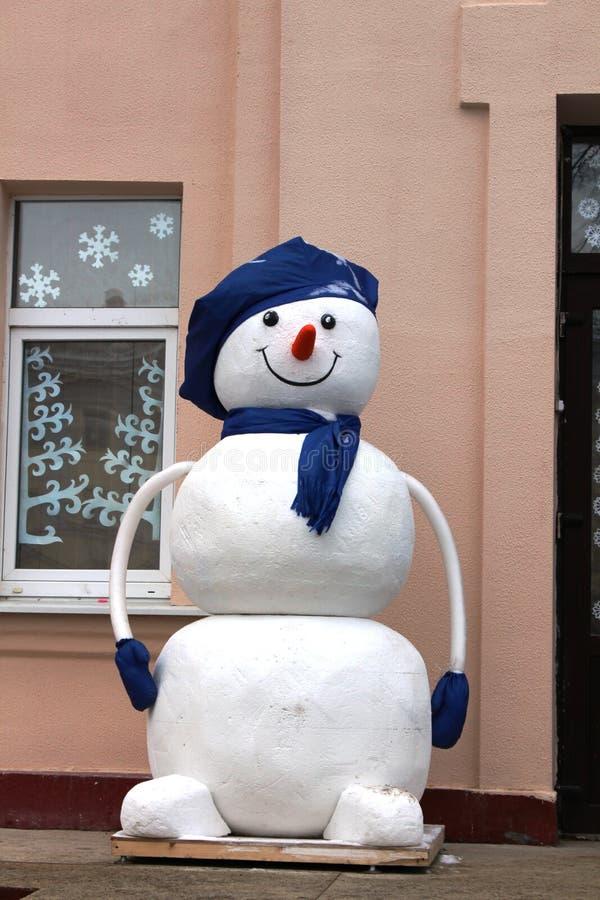 Ένας χιονάνθρωπος σε ένα μπλε καπέλο στοκ εικόνα με δικαίωμα ελεύθερης χρήσης