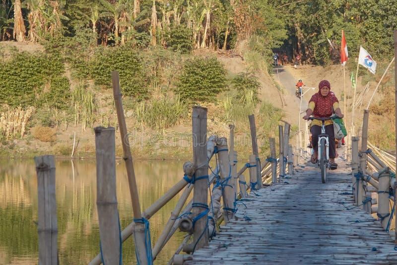 Ένας χωρικός που εργάζεται ως έμπορος στην παραδοσιακή αγορά που διασχίζει τη γέφυρα του μπαμπού στοκ φωτογραφία με δικαίωμα ελεύθερης χρήσης