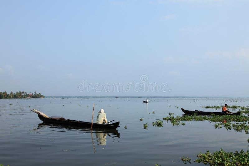Ένας χωρικός σε μια βάρκα κάνει την αλιεία στα τέλματα στοκ φωτογραφία