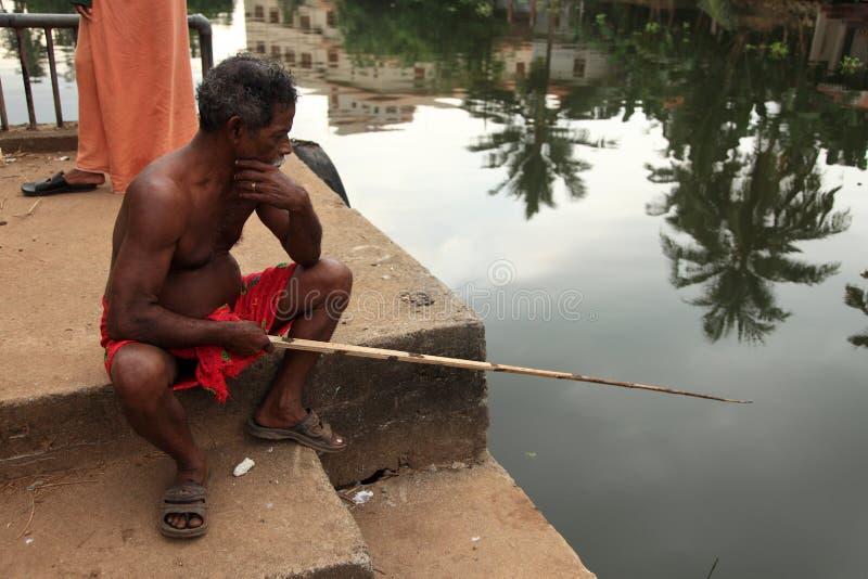 Ένας χωρικός χρησιμοποιεί μια ράβδο αλιείας για να αλιεύσει στα τέλματα στοκ εικόνα