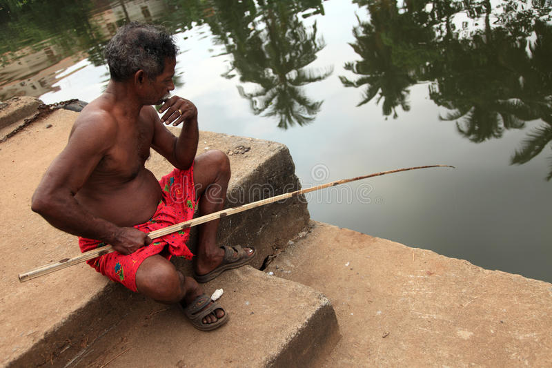 Ένας χωρικός χρησιμοποιεί μια ράβδο αλιείας για να αλιεύσει στα τέλματα στοκ εικόνες