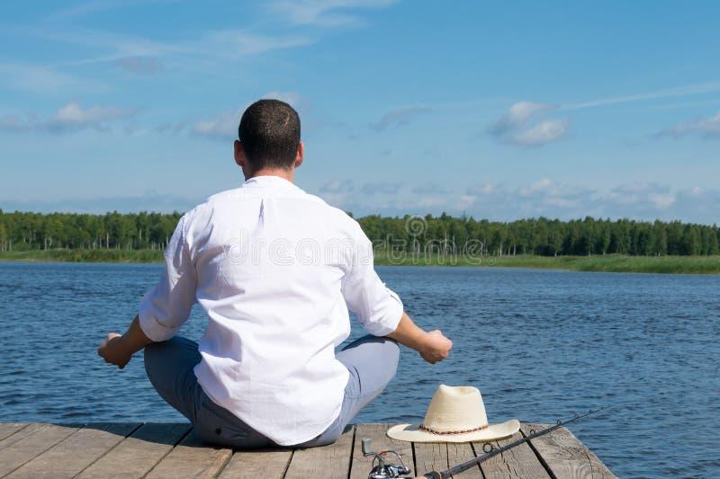 Ένας ψαράς κάθεται σε μια θέση λωτού της γιόγκας και σκέφτεται πώς να πιάσει τα ψάρια σε έναν ποταμό στοκ φωτογραφία με δικαίωμα ελεύθερης χρήσης