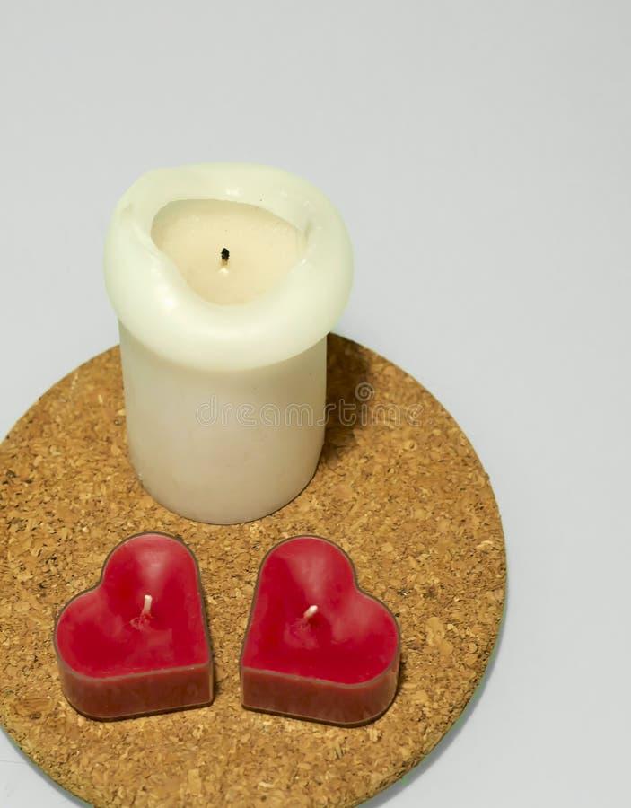 Ένας ψηλοί άσπρος και καρδιά δύο διαμόρφωσε τα κόκκινα κεριά στο στρογγυλό καυτό μαξιλάρι φελλού στο άσπρο υπόβαθρο στοκ φωτογραφία με δικαίωμα ελεύθερης χρήσης