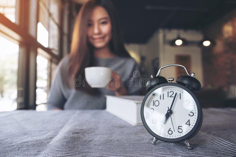 Ένας όμορφος ασιατικός καφές κατανάλωσης γυναικών το πρωί με το μαύρο ξυπνητήρι στοκ εικόνες