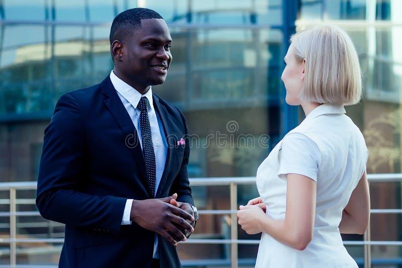 Ένας όμορφος Αφρικανός Αμερικανός επιχειρηματίας με ένα κομψό μαύρο κοστούμι μιλάει με μια ελκυστική ξανθιά γυναίκα επιχειρηματία στοκ φωτογραφίες