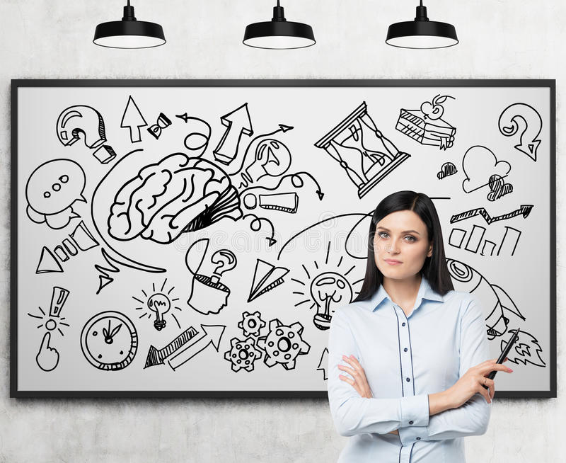 Ένας όμορφος επαγγελματίας brunette σκέφτεται για τη ανάπτυξη επιχείρησης Ένα σκίτσο ανάπτυξης επιχείρησης ή καταιγισμού ιδεών σύ στοκ εικόνες με δικαίωμα ελεύθερης χρήσης