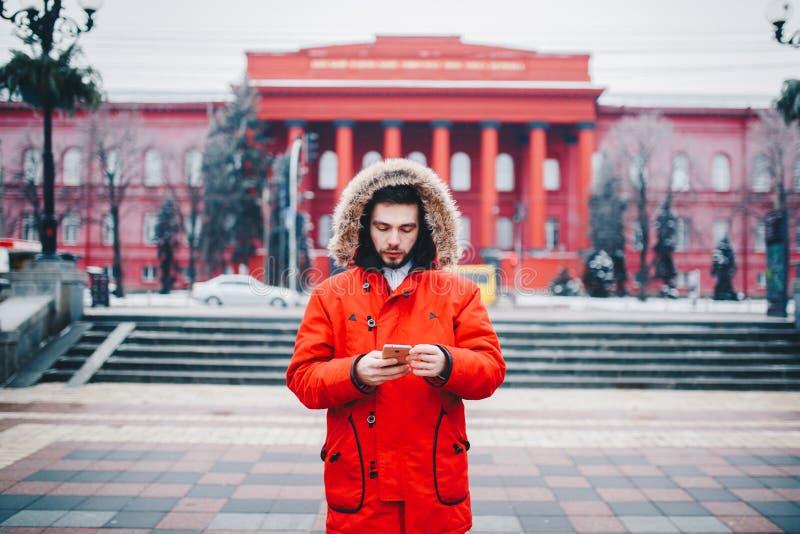 Ένας όμορφος νέος τύπος με τη γενειάδα και το κόκκινο σακάκι στην κουκούλα που ένας σπουδαστής χρησιμοποιεί ένα κινητό τηλέφωνο,  στοκ φωτογραφία