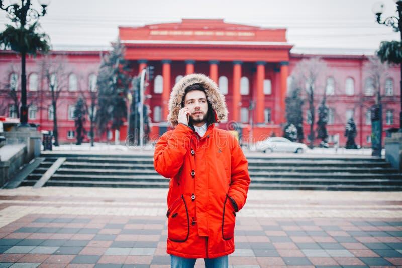 Ένας όμορφος νέος τύπος με τη γενειάδα και το κόκκινο σακάκι στην κουκούλα που ένας σπουδαστής χρησιμοποιεί ένα κινητό τηλέφωνο,  στοκ εικόνες