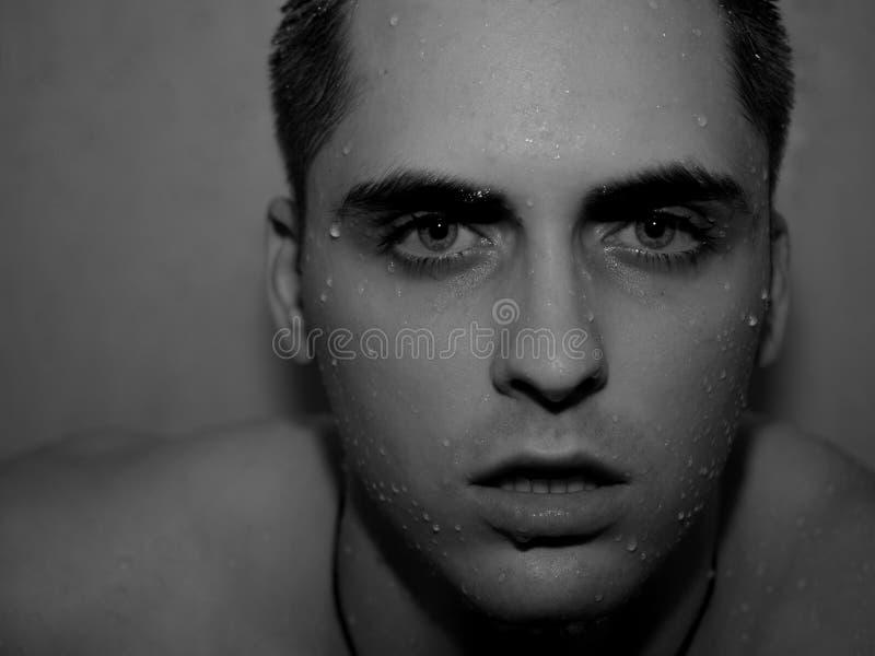 Ένας όμορφος νεαρός άνδρας κάτω από το στάλαγμα ντους υγρό στοκ φωτογραφία