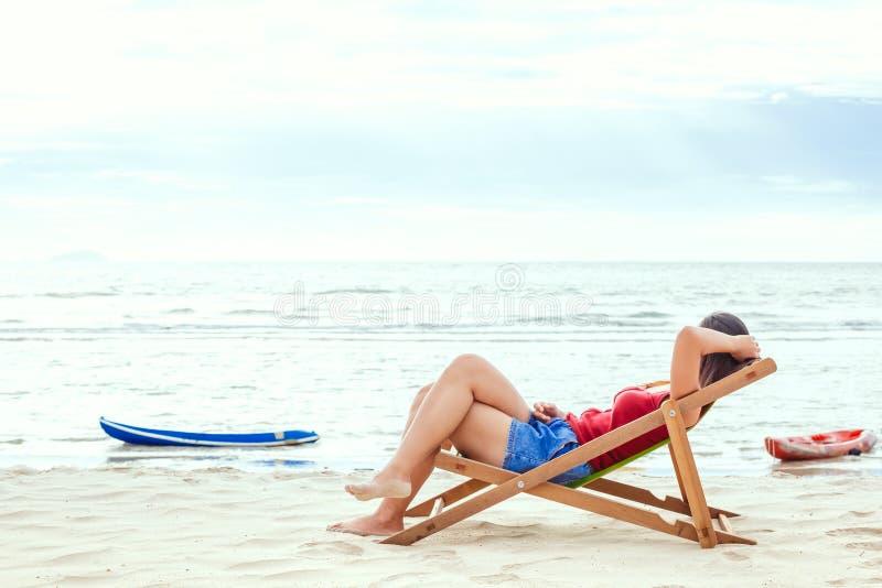 Ένας ύπνος γυναικών στην καρέκλα παραλιών με το μπλε ουρανό με το σύννεφο στοκ εικόνες