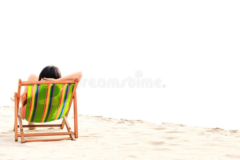 Ένας ύπνος γυναικών στην καρέκλα παραλιών με το μπλε ουρανό με το σύννεφο στοκ φωτογραφία