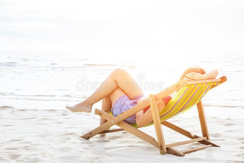 Ένας ύπνος γυναικών στην καρέκλα παραλιών στοκ φωτογραφία