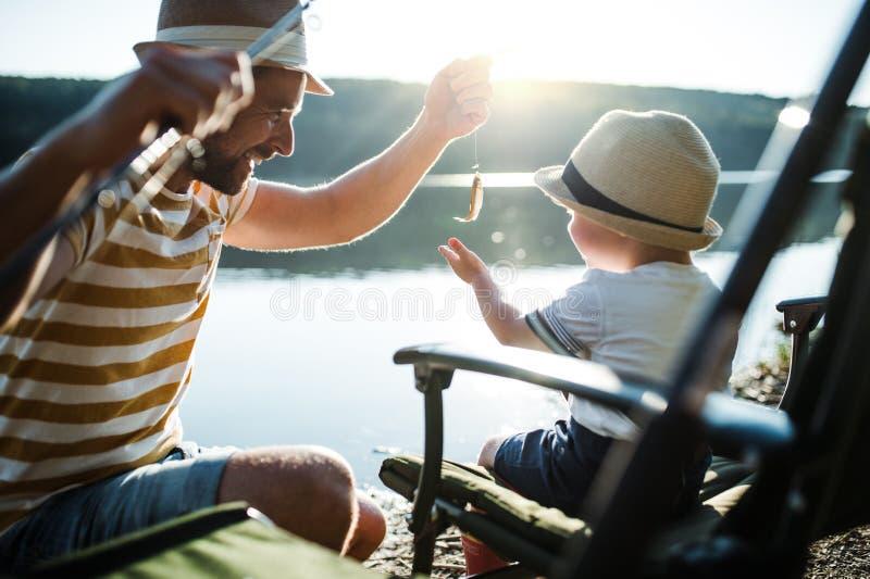 Ένας ώριμος πατέρας με έναν μικρό γιο μικρών παιδιών που αλιεύει υπαίθρια από μια λίμνη στοκ εικόνες