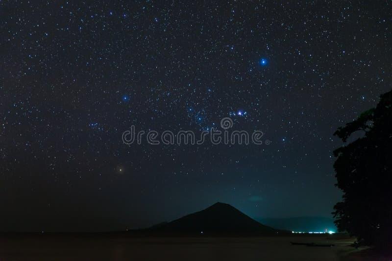 Έναστρα αστέρια ουρανού αστερισμού του Orion πέρα από το ηφαιστειακό νησί Gunung API που καίγεται στα τροπικά νησιά Moluccas της  στοκ φωτογραφίες