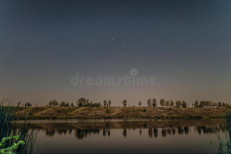 Έναστρη νύχτα πέρα από τη λίμνη στοκ φωτογραφία