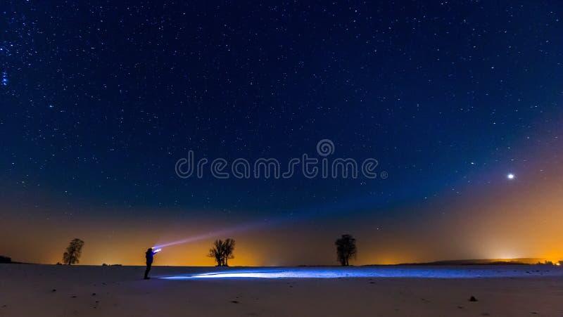 Έναστροι ουρανός και άτομο με το φακό να είστε μπορεί να σχεδιάσει το χρησιμοποιημένο νύχτα χειμώνα τοπίων απεικόνισής σας στοκ εικόνα
