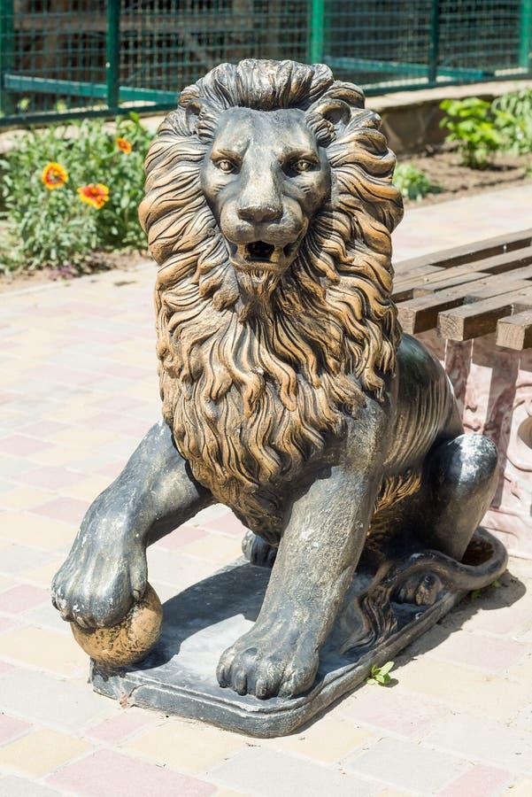 Ένα άγαλμα χαλκού ενός επιθετικού λιονταριού εξωραΐζει τη λεωφόρο στο πάρκο στοκ φωτογραφία με δικαίωμα ελεύθερης χρήσης