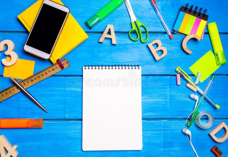 Ένα άσπρο σημειωματάριο στο γραφείο σπουδαστών ` s μεταξύ των σχολικών προμηθειών Διάστημα για το κείμενο, διάστημα αντιγράφων Η  στοκ εικόνες με δικαίωμα ελεύθερης χρήσης