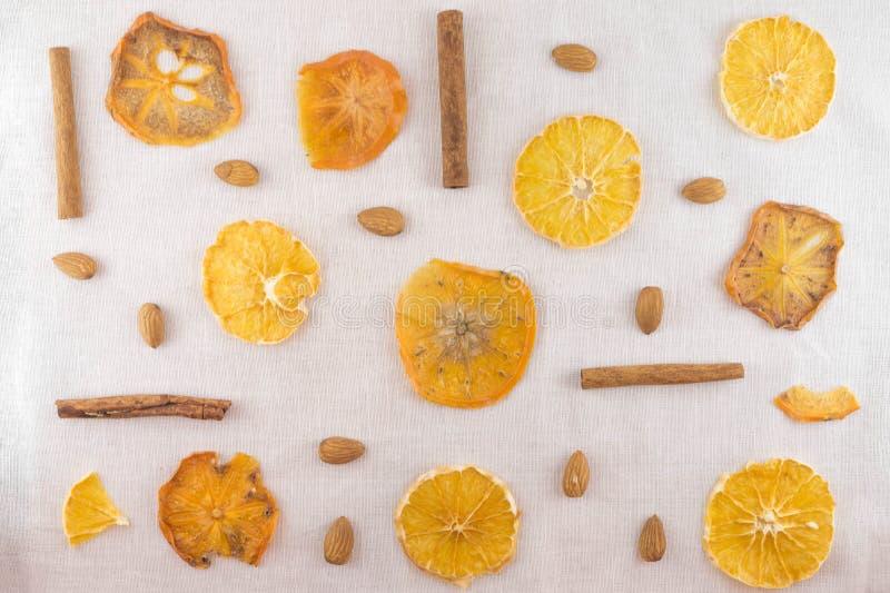 Ένα άσπρο υπόβαθρο σε ένα άνετο ύφος Φέτες του ξηρών πορτοκαλιού, persimmons και των αμυγδάλων r στοκ εικόνες
