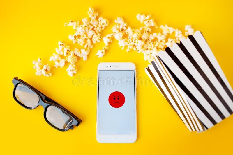 Ένα άσπρο smartphone με τα smilies στην οθόνη, τα τρισδιάστατα γυαλιά, ένα γραπτό ριγωτό κιβώτιο εγγράφου και διεσπαρμένο popcorn στοκ φωτογραφίες