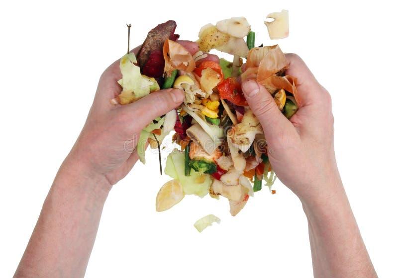 Ένα άστεγο άτομο επαιτών που σκάβει σε έναν σωρό των αποβλήτων τροφίμων σε μια απόρριψη στοκ φωτογραφία
