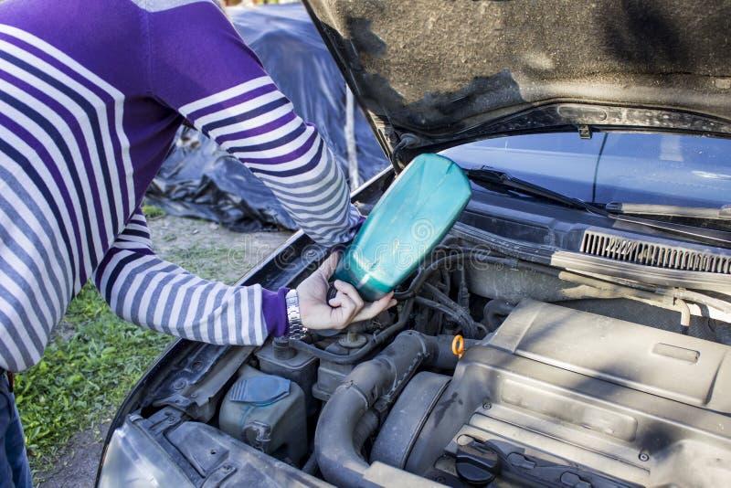 Ένα άτομο βάζει το πετρέλαιο στο αυτοκίνητο, η κουκούλα είναι ανοικτή στοκ εικόνα