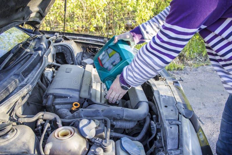 Ένα άτομο βάζει το πετρέλαιο στο αυτοκίνητο, η κουκούλα είναι ανοικτή στοκ φωτογραφία με δικαίωμα ελεύθερης χρήσης