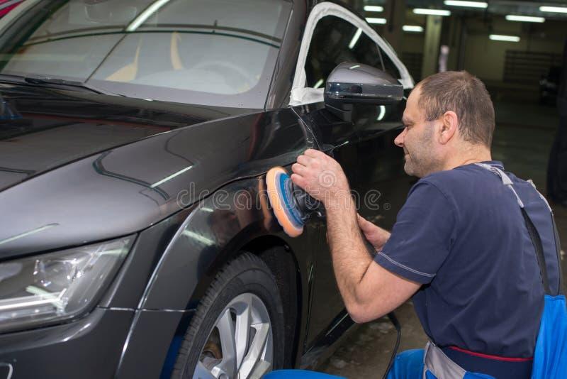Ένα άτομο γυαλίζει ένα μαύρο αυτοκίνητο στοκ φωτογραφία με δικαίωμα ελεύθερης χρήσης