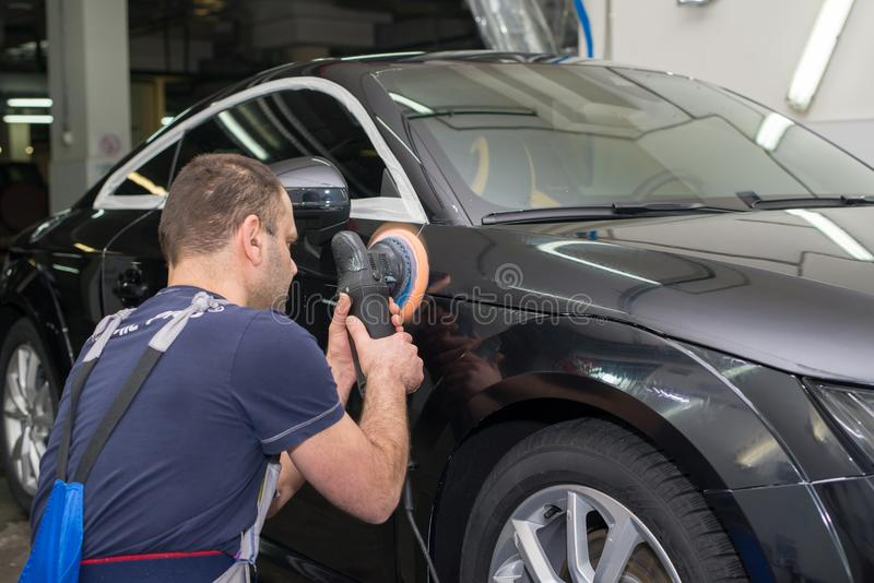 Ένα άτομο γυαλίζει ένα μαύρο αυτοκίνητο στοκ εικόνες με δικαίωμα ελεύθερης χρήσης