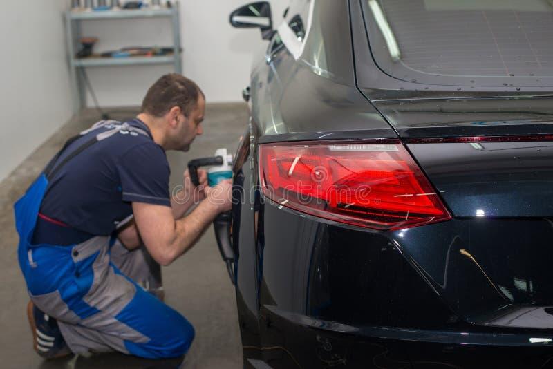 Ένα άτομο γυαλίζει ένα μαύρο αυτοκίνητο στοκ εικόνα με δικαίωμα ελεύθερης χρήσης