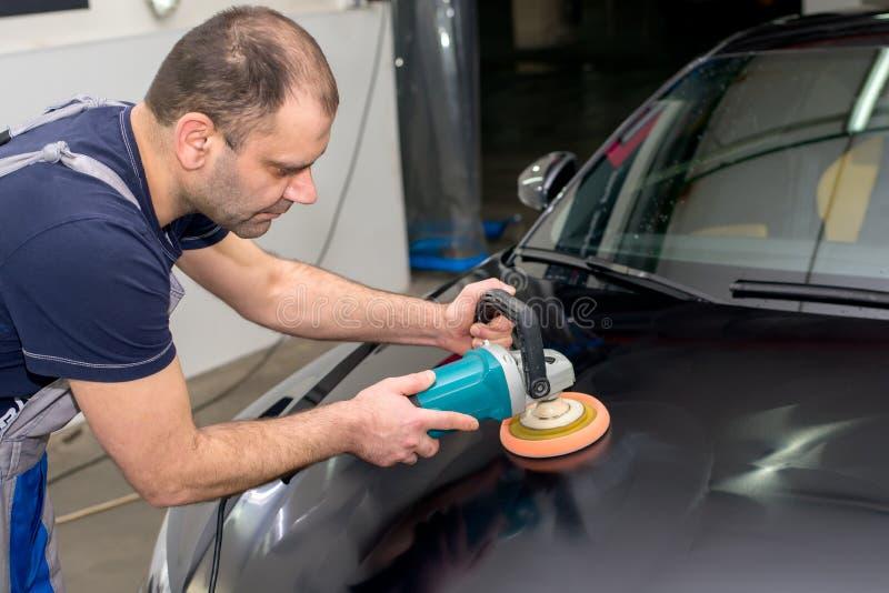 Ένα άτομο γυαλίζει ένα μαύρο αυτοκίνητο στοκ φωτογραφία