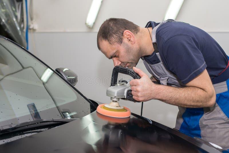 Ένα άτομο γυαλίζει ένα μαύρο αυτοκίνητο στοκ φωτογραφίες με δικαίωμα ελεύθερης χρήσης