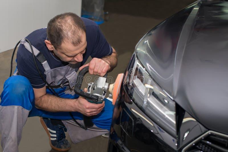 Ένα άτομο γυαλίζει ένα μαύρο αυτοκίνητο στοκ εικόνα