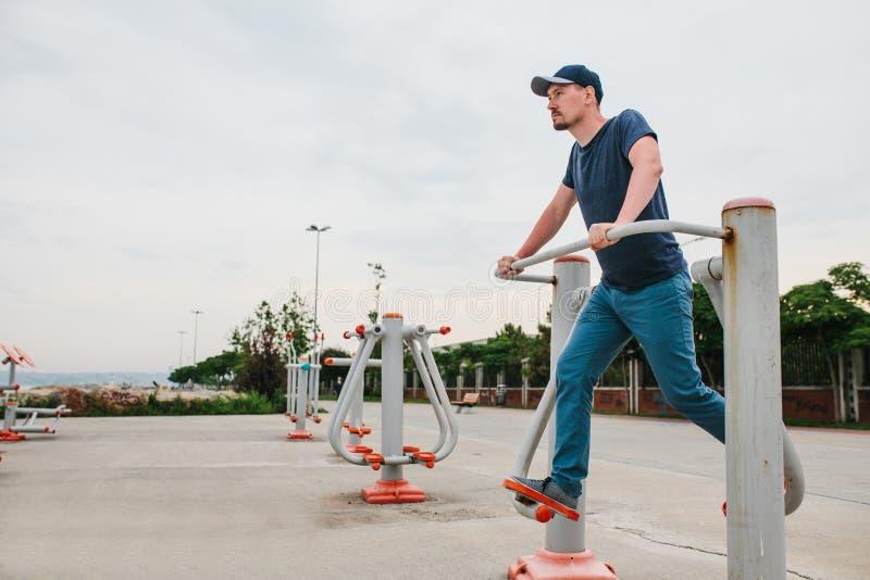 Ένα άτομο εκπαιδεύει στον αθλητικό εξοπλισμό σε μια πόλη υπαίθρια Η έννοια ενός υγιών τρόπου ζωής και μιας δυνατότητας πρόσβασης στοκ φωτογραφίες