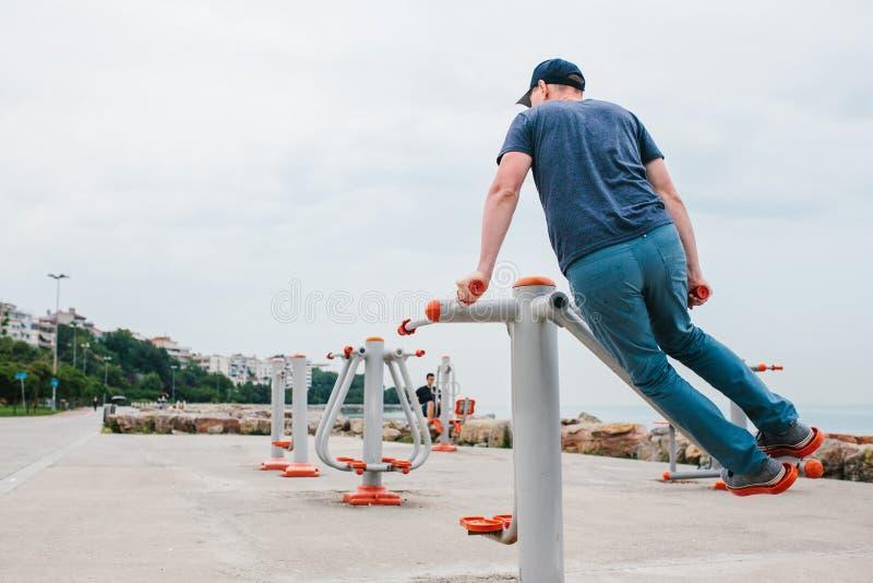 Ένα άτομο εκπαιδεύει στον αθλητικό εξοπλισμό σε μια πόλη υπαίθρια Η έννοια ενός υγιών τρόπου ζωής και μιας δυνατότητας πρόσβασης στοκ εικόνα