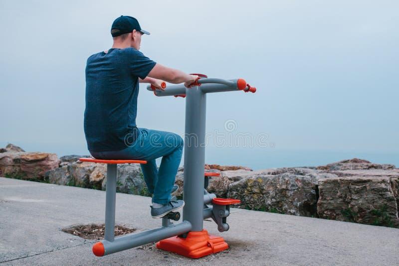 Ένα άτομο εκπαιδεύει στον αθλητικό εξοπλισμό σε μια πόλη υπαίθρια Η έννοια ενός υγιών τρόπου ζωής και μιας δυνατότητας πρόσβασης στοκ φωτογραφία