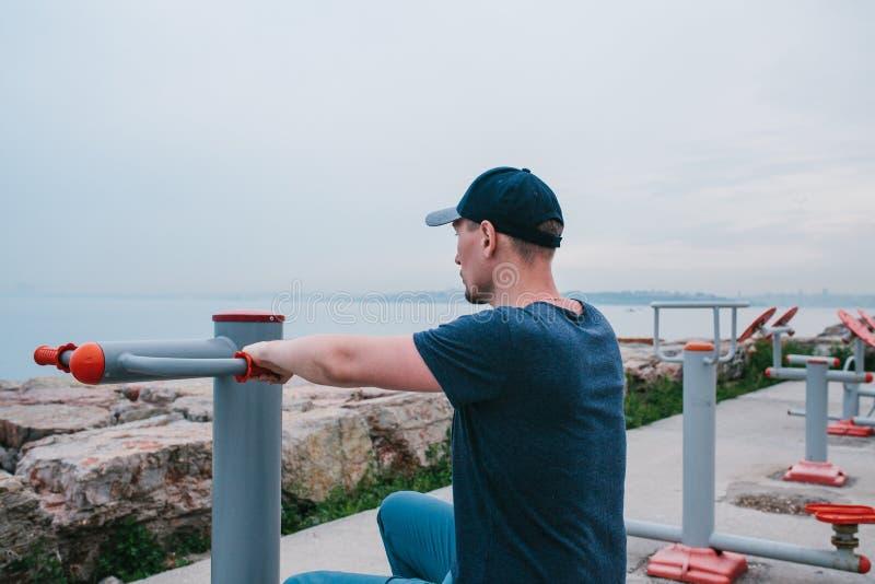 Ένα άτομο εκπαιδεύει στον αθλητικό εξοπλισμό σε μια πόλη υπαίθρια Η έννοια ενός υγιών τρόπου ζωής και μιας δυνατότητας πρόσβασης στοκ εικόνες