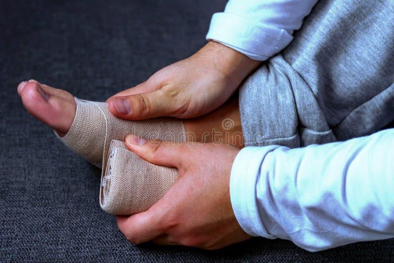 Ένα άτομο επιδένει το πόδι του με έναν αθλητικό επίδεσμο Τραυματισμοί και sprains στον αθλητισμό η υγεία προσοχής όπλων απομόνωσε στοκ φωτογραφίες