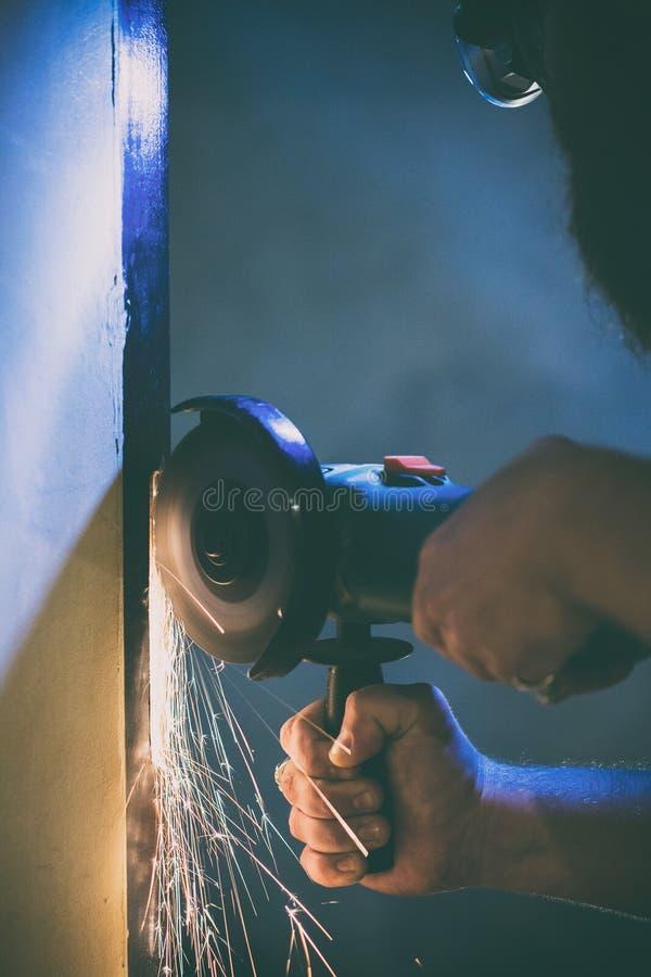 Ένα άτομο επισκευάζει μια πόρτα στο υπόγειο του σπιτιού του χρησιμοποιώντας μια χειρωνακτική αλέθοντας μηχανή στοκ εικόνες