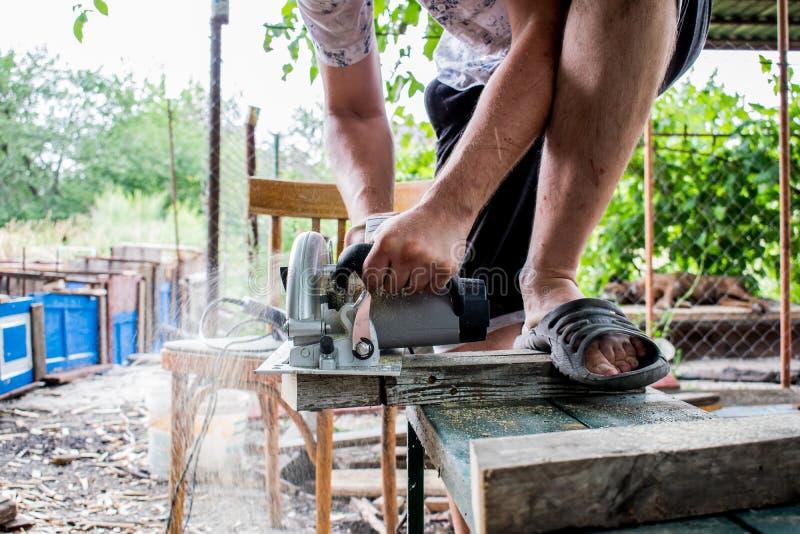 Ένα άτομο εργάζεται με τα χέρια του και ένα εργαλείο κατασκευής Ηλεκτρικό πριόνι Εργασία για τους ξύλινους πίνακες Για να κόψουν  στοκ εικόνες με δικαίωμα ελεύθερης χρήσης