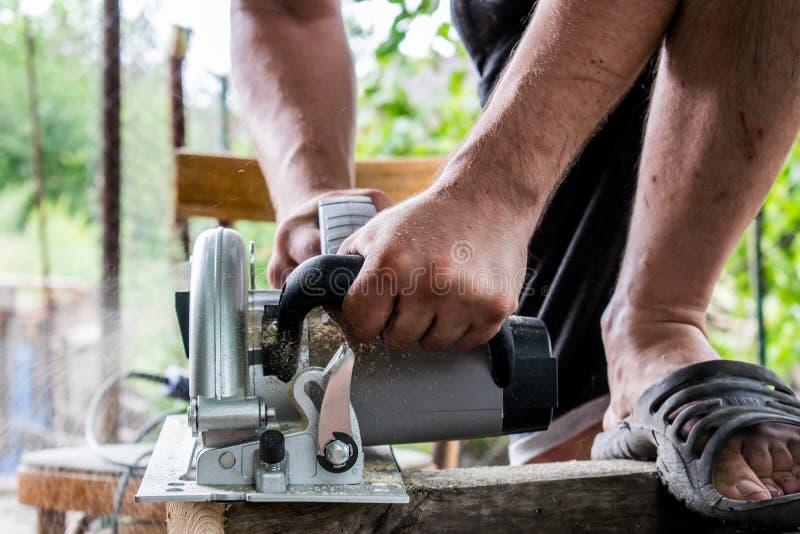 Ένα άτομο εργάζεται με τα χέρια του και ένα εργαλείο κατασκευής Ηλεκτρικό πριόνι Εργασία για τους ξύλινους πίνακες Για να κόψουν  στοκ εικόνες