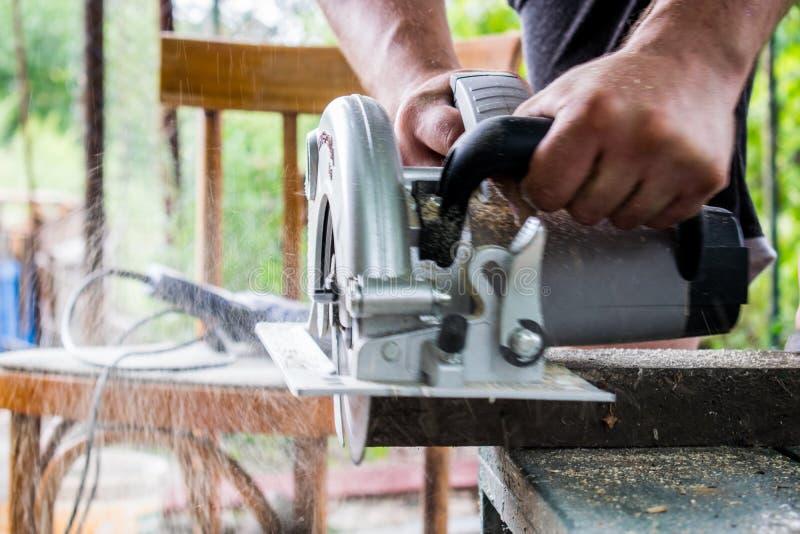 Ένα άτομο εργάζεται με τα χέρια του και ένα εργαλείο κατασκευής Ηλεκτρικό πριόνι Εργασία για τους ξύλινους πίνακες Για να κόψουν  στοκ εικόνα