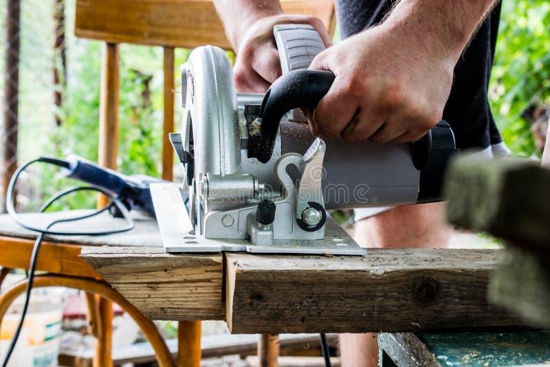 Ένα άτομο εργάζεται με τα χέρια του και ένα εργαλείο κατασκευής Ηλεκτρικό πριόνι Εργασία για τους ξύλινους πίνακες Για να κόψουν  στοκ φωτογραφίες