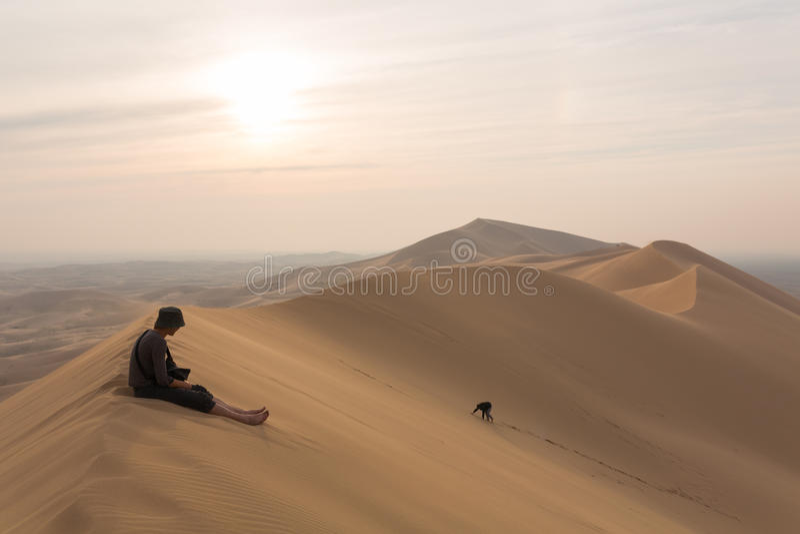 Ένα άτομο κάθεται πάνω από τους αμμόλοφους της ερήμου, και τις άλλες αναβάσεις στην κορυφή στοκ εικόνες με δικαίωμα ελεύθερης χρήσης