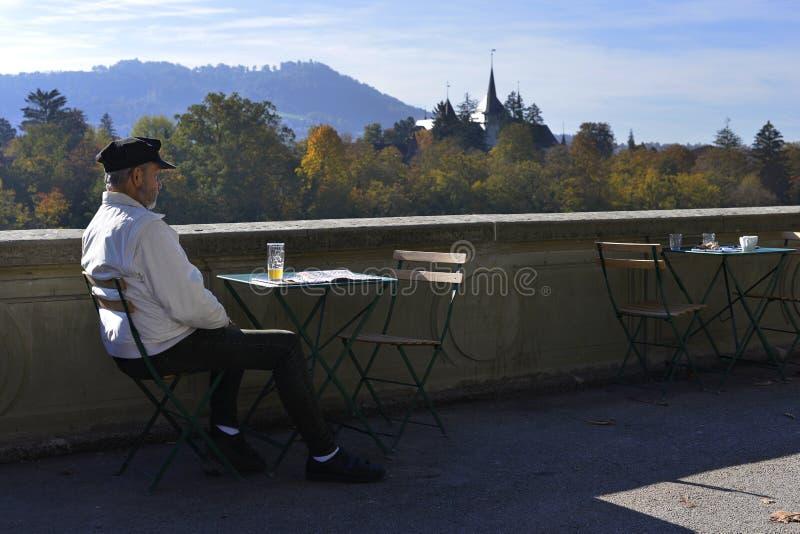 Ένα άτομο κάθεται σε έναν πίνακα καφέδων στοκ φωτογραφίες