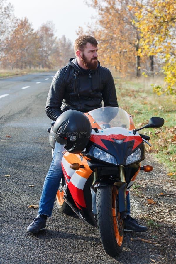 Ένα άτομο κάθεται σε ένα πορτοκαλί ποδήλατο στοκ φωτογραφία