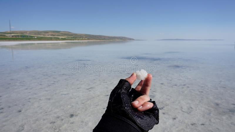 Ένα άτομο κρατά μια αλατισμένη νιφάδα στο Σόλτ Λέικ, Τουρκία Ένα άτομο κρατά κάτι στοκ εικόνα με δικαίωμα ελεύθερης χρήσης