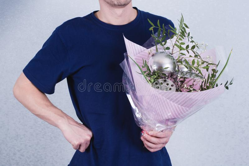 Ένα άτομο κρατά μια ανθοδέσμη των λουλουδιών και των κουταλών έννοια της πατριαρχικής ανισότητας κοινωνίας και γένους Sexism και  στοκ εικόνα